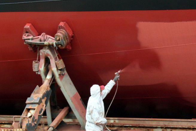 Applicateur peignant une coque de bateau